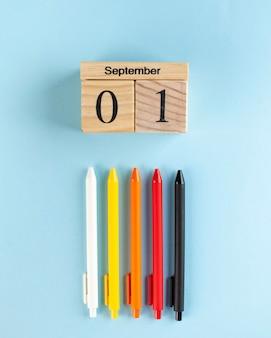 Drewniany kalendarz na 1 września, kolorowe długopisy na niebieskiej powierzchni. koncepcja plastyczna początku roku szkolnego.