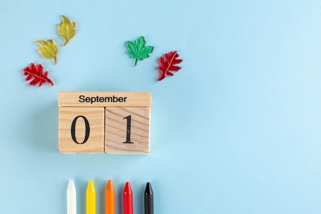 Drewniany kalendarz na 1 września, kolorowe długopisy. skopiuj miejsce. koncepcja plastyczna początku roku szkolnego.