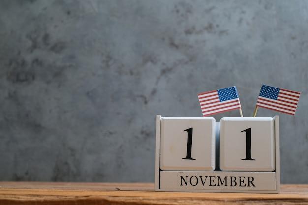 Drewniany kalendarz na 11 listopada z miniaturowymi amerykańskimi flagami. koncepcje obchodów światowego dnia weterana