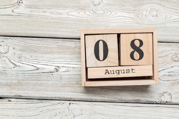 Drewniany kalendarz w kształcie sześcianu na 8 sierpnia na drewnianym