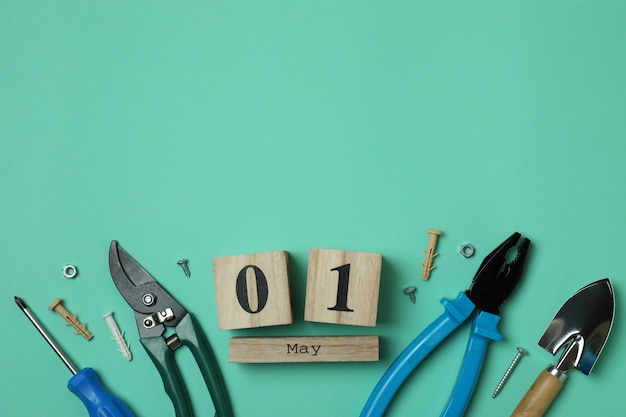 Drewniany kalendarz z 1 maja i narzędziami na miętowym tle