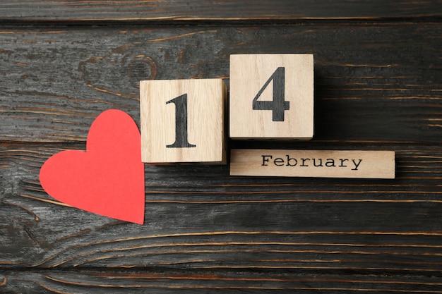 Drewniany kalendarz z 14 lutego i papierowym sercem na drewnianym tle