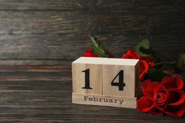 Drewniany kalendarz z 14 lutego i różami na drewnianym tle