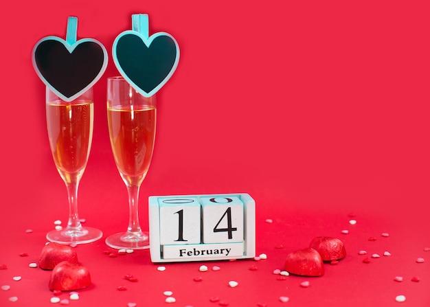 Drewniany kalendarz z datą 14 lutego i dwoma kieliszkami do szampana