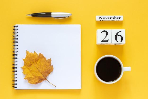 Drewniany kalendarz z filiżanką kawy i notatnikiem