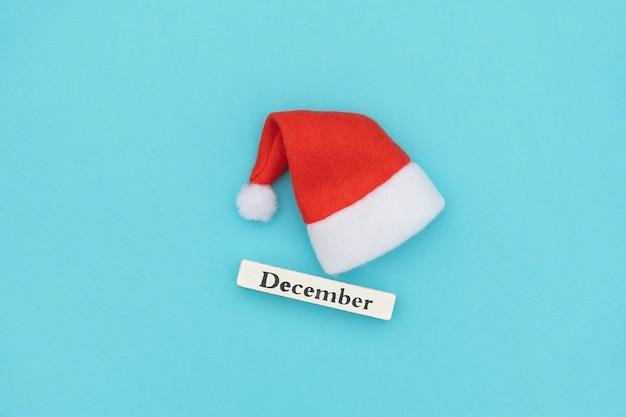 Drewniany kalendarz zimowy miesiąc grudnia i kapelusz santa na niebieskim papierze