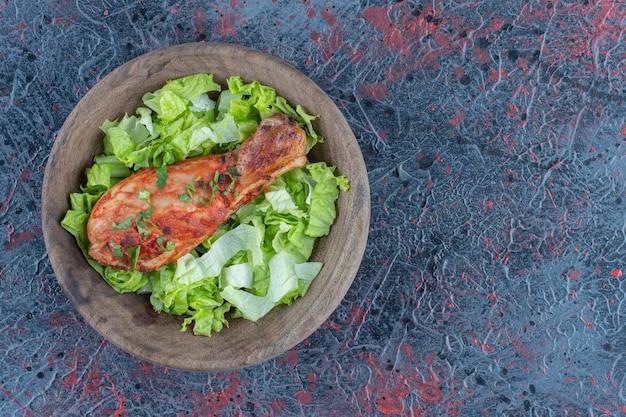 Drewniany kawałek pysznego mięsa z nogi kurczaka z sałatką jarzynową