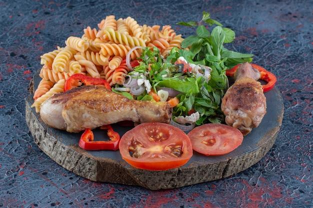 Drewniany kawałek smażonego mięsa z nogi kurczaka z surówką jarzynową.