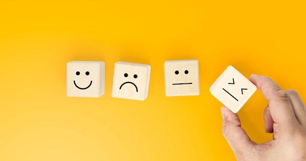 Drewniany klocek posiada emotikon dla klientów oceniających ich zadowolenie z usługi, kopie miejsca na obrazy reklamowe, izolowany na żółtym tle oraz ścieżkę przycinającą.
