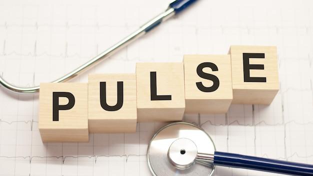 Drewniany klocek tworzący słowo puls ze stetoskopem na pulpicie lekarza. koncepcja opieki zdrowotnej dla szpitala, kliniki i biznesu medycznego