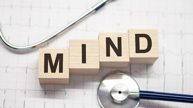 Drewniany klocek tworzący słowo umysł ze stetoskopem na pulpicie lekarza. koncepcja medyczna. koncepcja opieki zdrowotnej dla szpitala, kliniki i biznesu medycznego