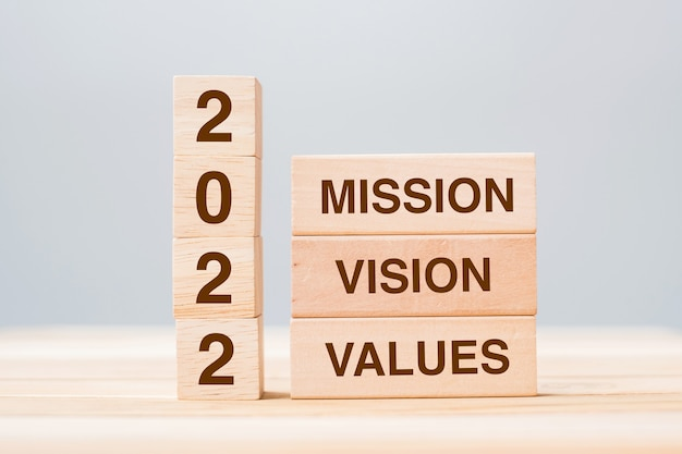 Drewniany klocek z napisem 2022 misja, wizja i wartość na tle stołu. koncepcje rozdzielczości, strategii, rozwiązania, celu, biznesu i świąt sylwestrowych