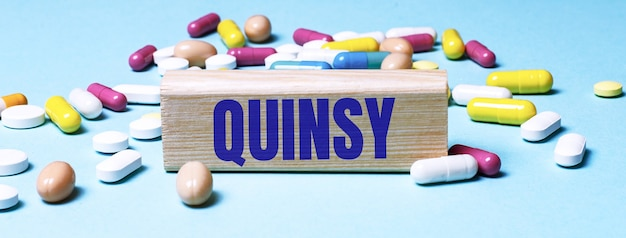 Drewniany klocek z napisem quinsy stoi na niebieskiej powierzchni wśród wielokolorowych pigułek