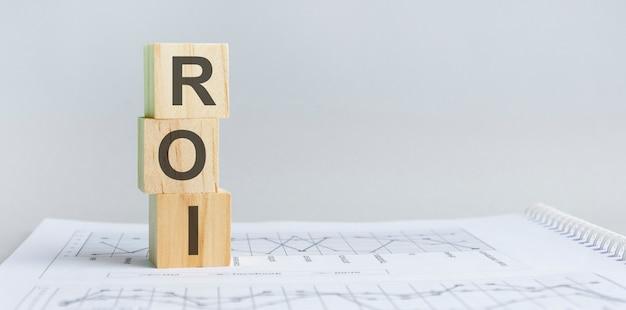 Drewniany klocek z napisem roi - akronim - zwrot z inwestycji. drewniane klocki roi znajdują się na papierowym szarym tle. pomysł na biznes. miejsce na tekst po prawej stronie. przedni widok.