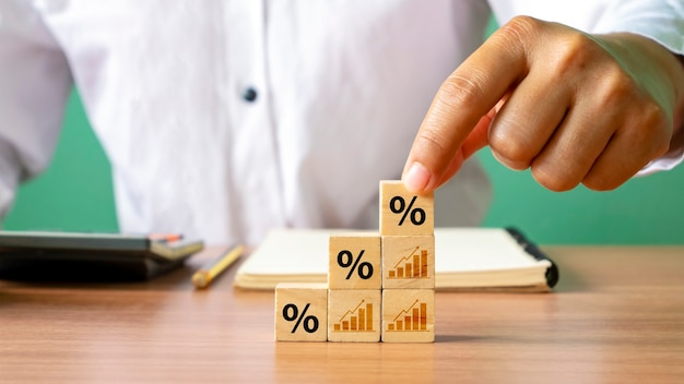 Drewniany klocek z symbolami procentowymi rośnie, a gospodarka poprawia się finansowo