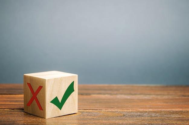 Drewniany klocek z zielonym znacznikiem wyboru. pojęcie wyboru i podejmowanie właściwej decyzji.