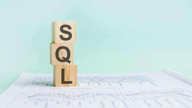 Drewniany klocek ze słowami sql - akronim sql - structured query language. drewniane klocki sql są na szarym tle papieru. pomysł na biznes. miejsce na tekst po prawej stronie. przedni widok
