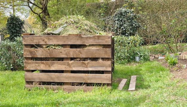 Drewniany kompostownik pełen odpadów w ogrodzie