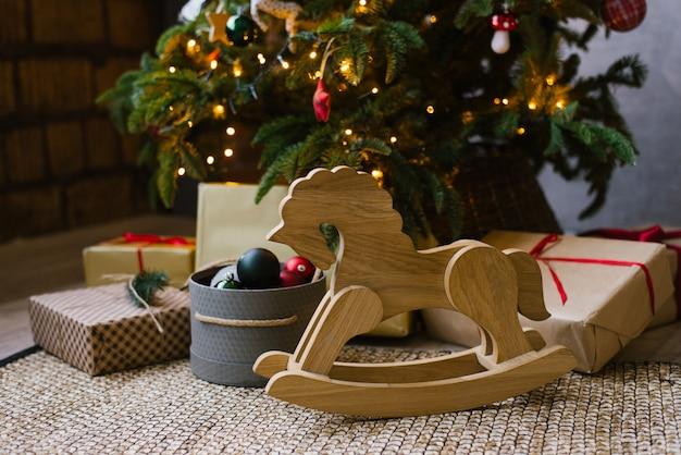 Drewniany koń na biegunach dla dzieci stoi obok świątecznych prezentów pod choinką z lampkami