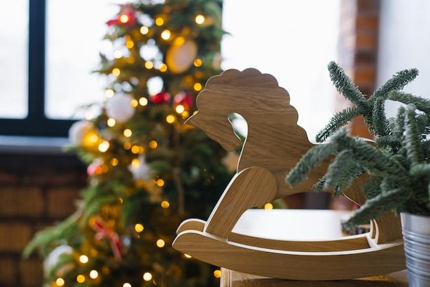 Drewniany koń zabawkowy i świąteczne świerki