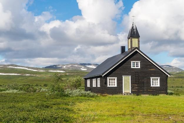 Drewniany kościół na zielonej łące na tle pochmurnego nieba, finnmark, norwegia