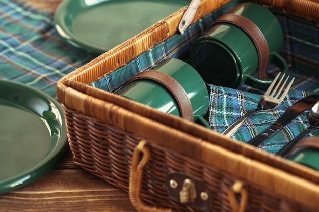 Drewniany kosz na piknik z talerzami, filiżankami i sztućcami z bliska