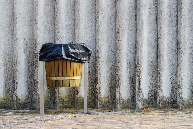 Drewniany kosz na śmieci na szarym tle ściany betonowej