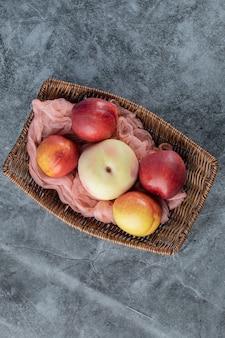 Drewniany kosz owoców z jabłkami i czerwonymi brzoskwiniami