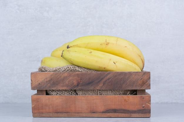 Drewniany kosz pełen bananów dojrzałych owoców na białym tle