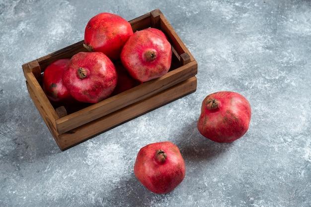 Drewniany kosz pełen słodkich dojrzałych owoców granatu.