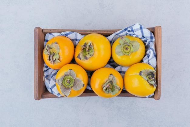 Drewniany kosz pełen słodkich persimmons na białym tle. zdjęcie wysokiej jakości