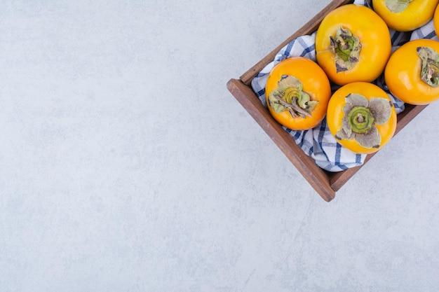Drewniany kosz pełen słodkich persymonów na białym tle.
