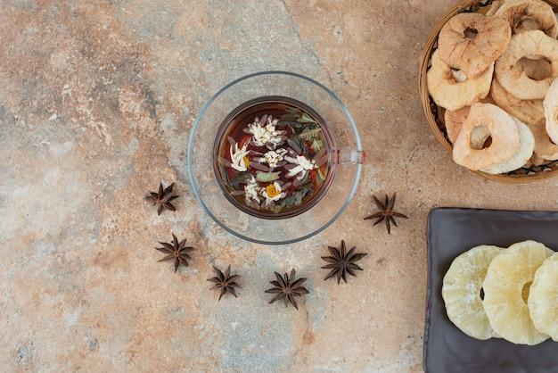 Drewniany kosz pełen suszonego ananasa i filiżanki herbaty ziołowej