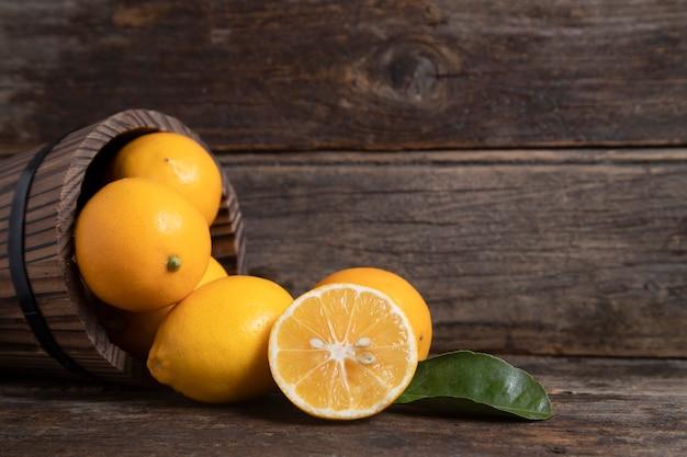 Drewniany kosz pełen świeżych owoców cytryny z liśćmi umieszczony na drewnianym stole. wysokiej jakości zdjęcie