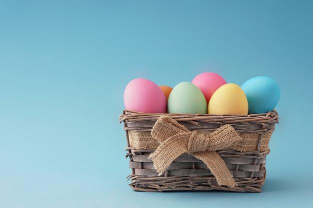 Drewniany kosz z pięknymi kolorowymi jajkami wesołych świąt, dobry blank na kartkę z życzeniami.