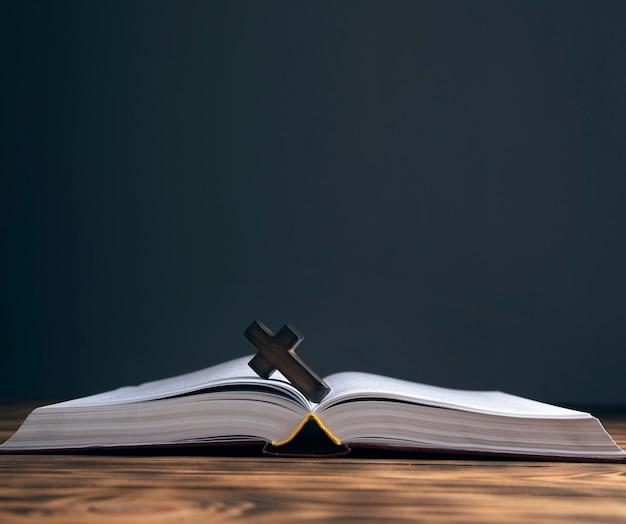 Drewniany krzyż na biblii na drewnianym stole.