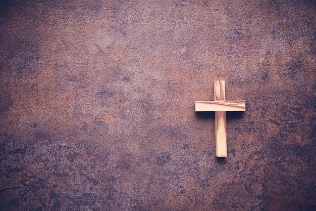 Drewniany krzyż na ciemnej kopii przestrzeni tonowania tle