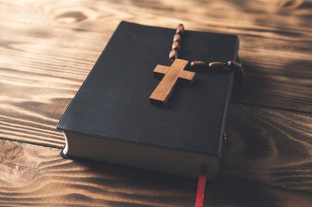 Drewniany krzyż na pismo święte na drewnianym stole