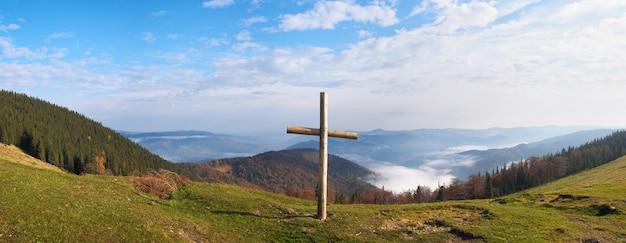 Drewniany krzyż na płaskowyżu góry jesienią. zdjęcie złożone z czterech ujęć. przedmieście jaremcze-miasta, obwód iwano-frankowsk, ukraina.