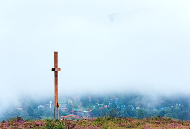 Drewniany krzyż na szczycie wzgórza letniego kwiatu wrzosu i mglisty poranek z tyłu