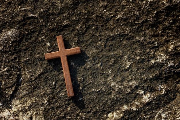Drewniany krzyż na tle kamieni.