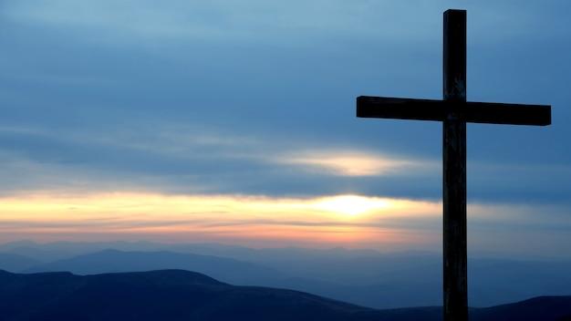 Drewniany krzyż na wschód słońca w górach. niesamowita przyroda i krajobrazy