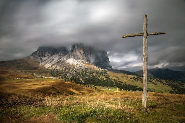 Drewniany krzyż na wzgórzu porośniętym zielenią z dolomitami w południowym tyrolu