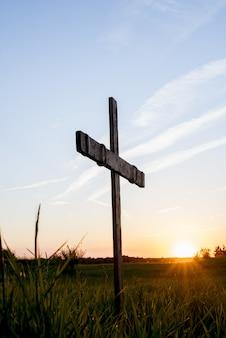 Drewniany krzyż w trawiastym polu z słońcem błyszczy w niebieskim niebie