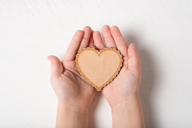 Drewniany kształt serca w dłoniach dla dzieci na białym tle