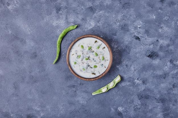 Drewniany kubek zupy jogurtowej z fasolą na niebieskim stole.