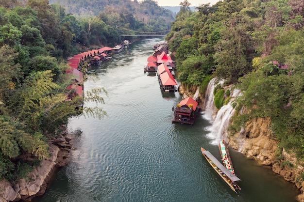 Drewniany łódkowaty żeglowanie rzeki kwai z siklawą w tropikalnym tropikalnym lesie deszczowym