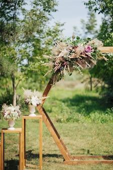 Drewniany łuk ślubny ozdobiony kwiatami stoi w lesie