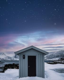 Drewniany magazyn i kolorowe niebo z gwiazdami na wybrzeżu w zimie na wyspie senja, norwegia