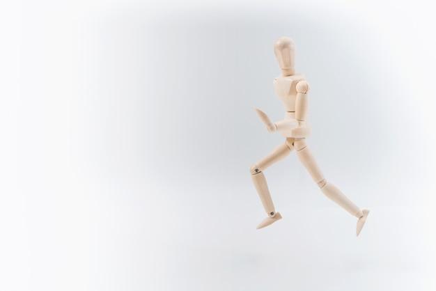 Drewniany manekin dumnie prezentuje jakąś niewidzialną rzecz, odizolowaną